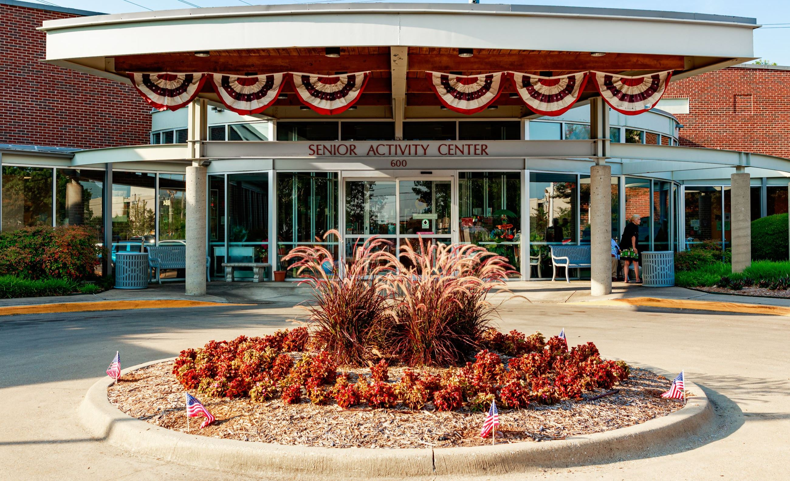 Front entrance of Garland Senior Activity Center with pretty flowers in front drive turnaround